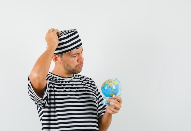 스트라이프 티셔츠 모자에서 생각하고 조심스럽게 보는 동안 지구본을 들고 젊은 남자