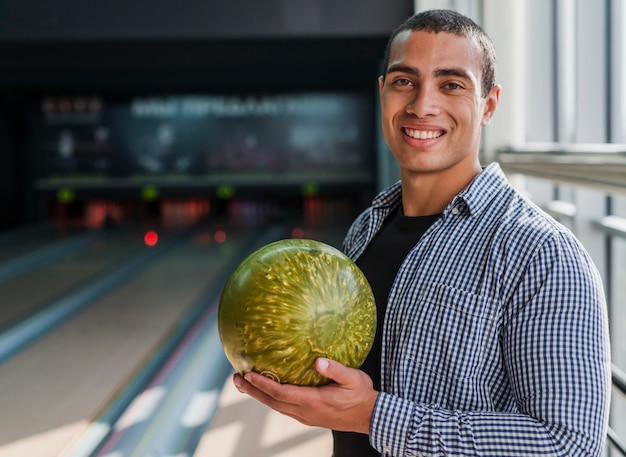 Young man holding a golden bowling ball