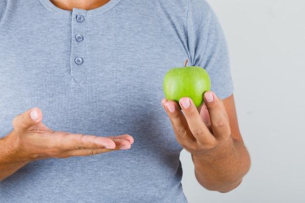 Молодой человек держит зеленое яблоко в серой футболке, вид спереди.