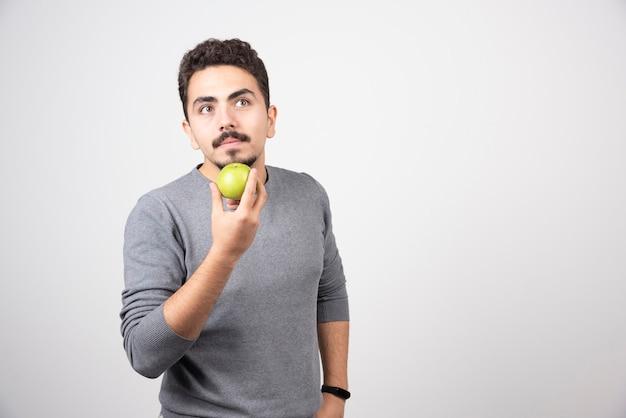 Giovane che tiene mela verde e pensiero.