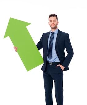 Молодой человек держит зеленый знак стрелки