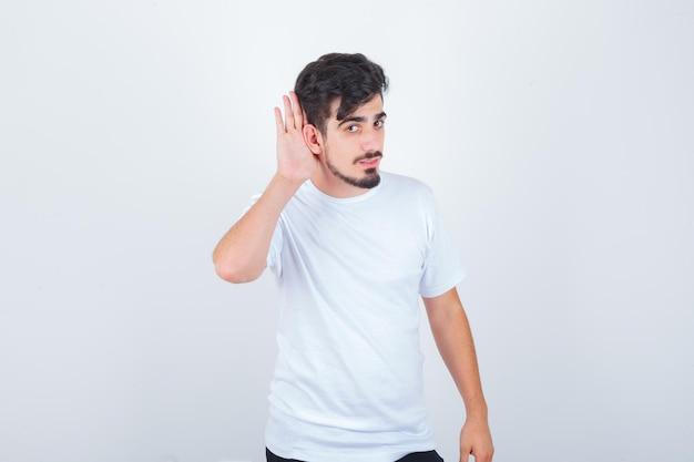 젊은 남자 티셔츠에 귀 뒤에 손을 잡고 자신감을 찾고