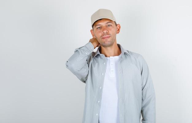 Молодой человек держит руку за голову в футболке и кепке