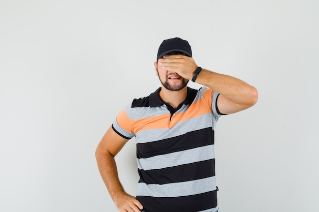 Giovane che tiene la mano sugli occhi in t-shirt, berretto e sembra eccitato, vista frontale.