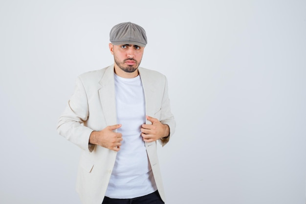 Giovane che tiene la mano sulla giacca in maglietta bianca, giacca e berretto grigio e sembra serio. vista frontale.