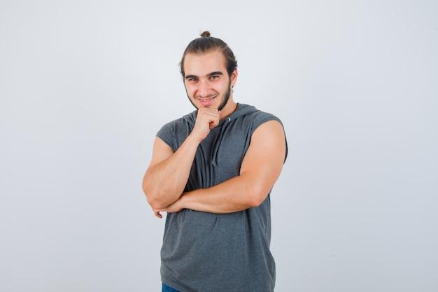 Молодой человек держит руку на подбородке в футболке с капюшоном и выглядит довольным, вид спереди.