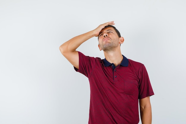티셔츠를 입은 이마에 손을 대고 절망적인 표정을 짓고 있는 청년. 전면보기.