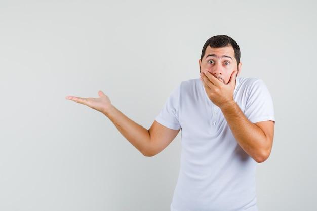 Tシャツで脇を指して驚いて見ている間、彼の口に手を握っている若い男、正面図。