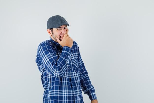 셔츠, 모자 전면보기에 웃으면 서 입에 손을 잡고 젊은 남자.