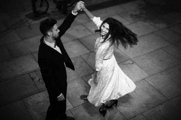Young man holding hand of whirling elegant cheerful woman