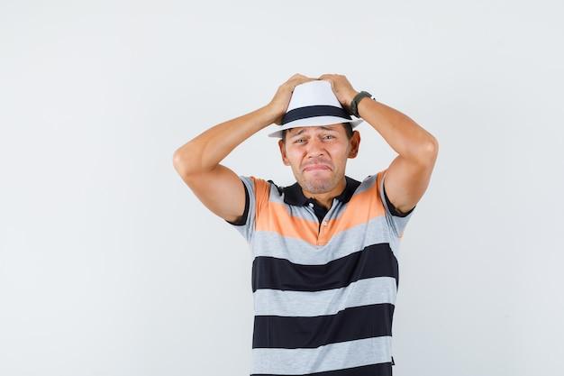 Giovane che tiene le mani sulla testa in t-shirt e cappello e sembra triste