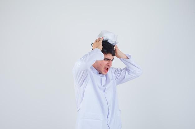 Giovane che tiene le mani sulla testa con il cappuccio in uniforme bianca e che sembra nervoso. vista frontale.