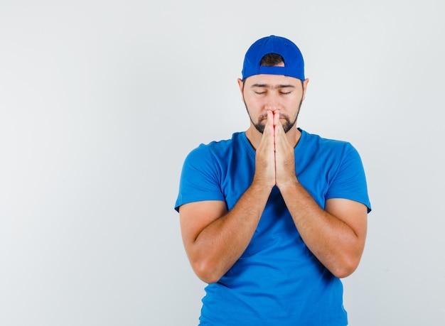Молодой человек, взявшись за руки в молитвенном жесте в синей футболке и кепке, выглядит спокойным