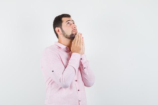 ピンクのシャツで祈りのジェスチャーで手をつないで、希望に満ちた若い男