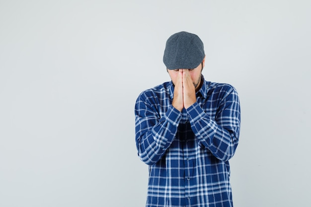 シャツ、キャップ、希望に満ちた正面図で祈りのジェスチャーで手をつないで若い男。