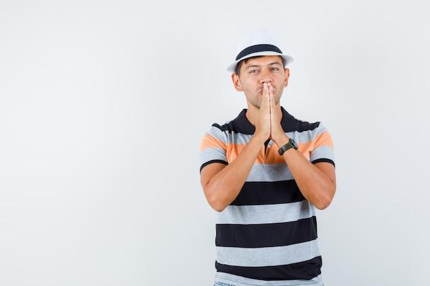 Tシャツと帽子でジェスチャーを祈って手をつないで、希望に満ちた若い男