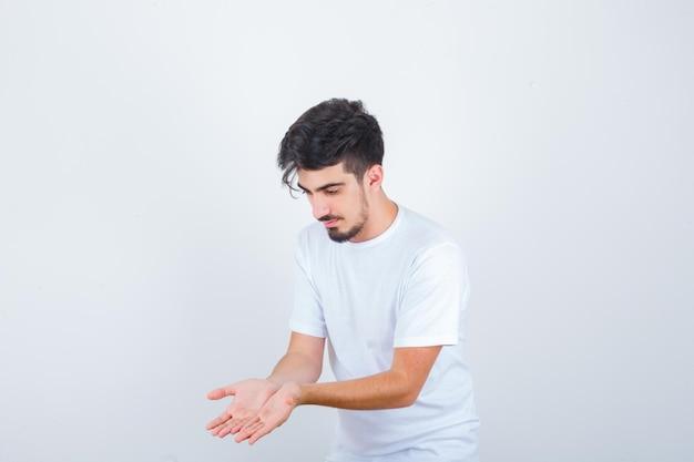 白いtシャツでジェスチャーを祈って手をつないで、希望に満ちた若い男