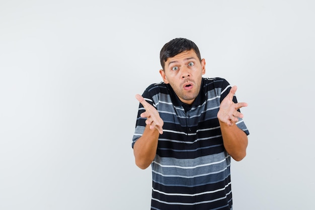 Молодой человек, вопросительно взявшись за руки в футболке и глядя в шоке, вид спереди.