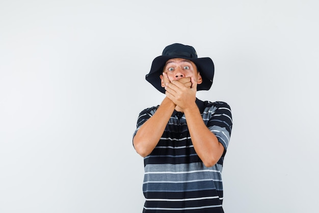 Young man holding hands on mouth in t-shirt, hat and looking scared. front view.