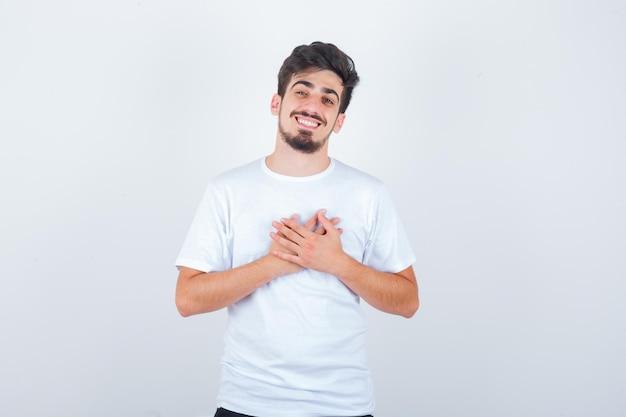 白いtシャツを着て胸に手をつないで元気に見える若い男
