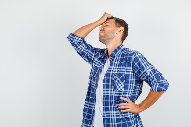 Молодой человек, держащий руки на лбу и талии в рубашке и выглядящий с сожалением. передний план.