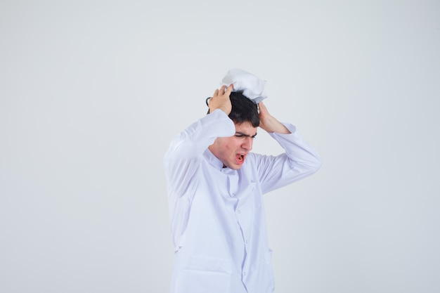 白い制服を着て、緊張しているように見えるキャップで頭に手をつないで若い男