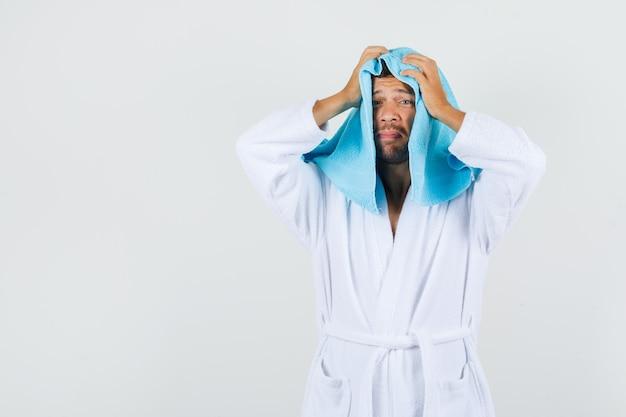 Молодой человек, держащий руки на голове с полотенцем в белом халате и беспомощный, вид спереди.