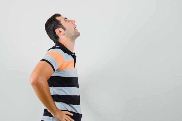 젊은 남자가 그의 허리에 손을 잡고 t- 셔츠를보고 지루해. 텍스트를위한 여유 공간