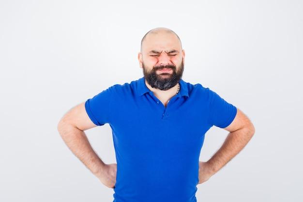 青いシャツを着て腰に手をつないで、痛みを伴う、正面図を探している若い男。