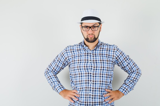 젊은 남자 체크 셔츠, 모자에 허리에 손을 잡고 무단, 전면보기를 찾고.