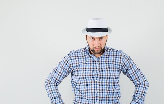체크 셔츠, 모자에 허리에 손을 잡고 엄격한, 전면보기를 찾고 젊은 남자.