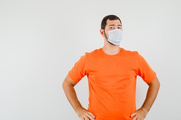 주황색 티셔츠, 마스크를 쓰고 자신감을 보이는 젊은 남자. 전면보기.