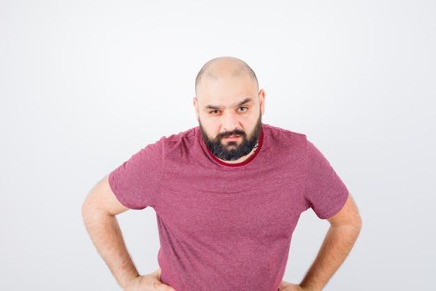 분홍색 티셔츠를 입고 허리에 손을 대고 진지한 표정을 짓고 있는 젊은 남자. 전면보기.