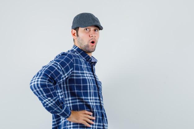 Молодой человек, взявшись за руки на талии в рубашке, кепке и выглядя удивленным.