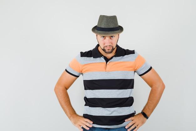 젊은 남자 t- 셔츠, 모자에 허리에 손을 잡고 엄격한, 전면보기를 찾고.