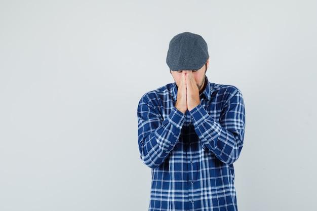 Giovane che si tiene per mano nel gesto di preghiera in camicia, berretto e guardando speranzoso, vista frontale.
