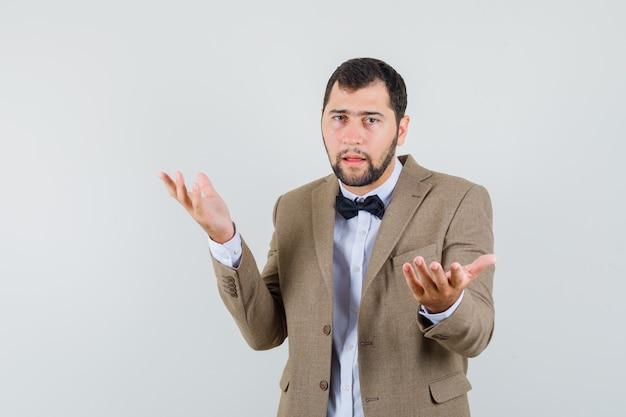 Giovane che tiene le mani nel gesto interrogativo in vestito e che sembra confuso. vista frontale.