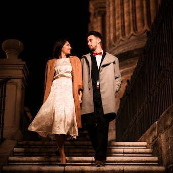 Young man holding hands with elegant woman and going down on steps