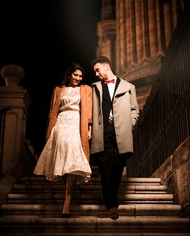 Young man holding hands with happy elegant woman and going down on steps