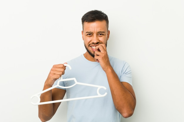 Young man holding a hanger biting fingernails, nervous and very anxious