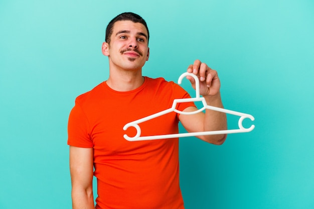 Young man holding a hanger isolated on blue wall dreaming of achieving goals and purposes