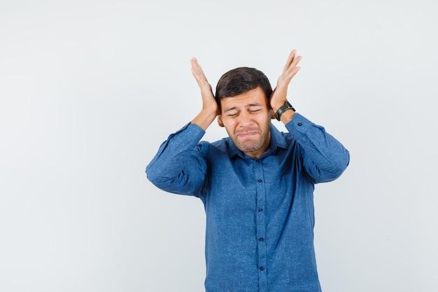 青いシャツを着て両手で頭を抱えてイライラしている若い男。正面図。