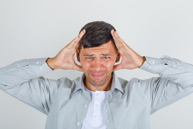 Молодой человек держит голову руками в рубашке и выглядит болезненно.