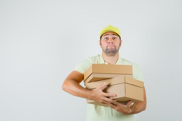 Tシャツのキャップで重い段ボール箱を保持している若い男