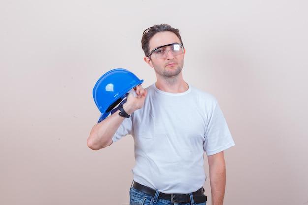 Молодой человек держит шлем в футболке, джинсах и выглядит серьезно