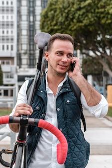 Молодой человек держит свой велосипед и разговаривает по телефону