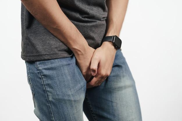 下痢、失禁、前立腺炎、性病に苦しんでいる彼の股を保持している若い男。ヘルスケアの概念。