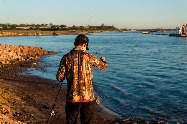 Молодой человек держит удочку с рыбкой.