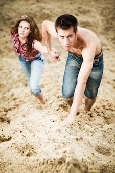 Молодой человек держит свою девушку за руку и поднимается на песчаный холм