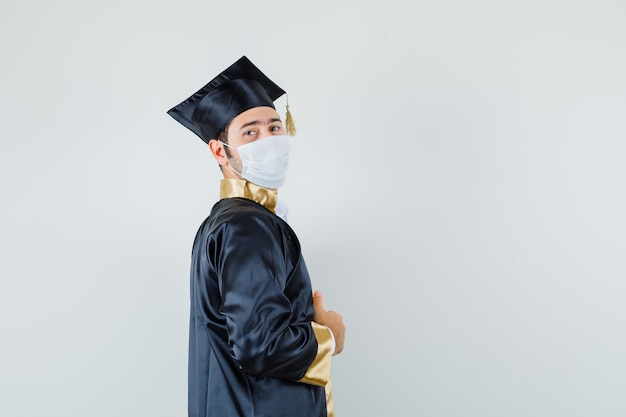 Young man holding his gown in graduate uniform and looking proud .